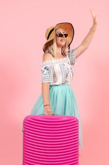 Vista frontale giovane donna che si prepara per le vacanze estive con borsa rosa sullo sfondo rosa viaggio a colori viaggio in aereo resto