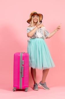 Vista frontale giovane donna che si prepara per le vacanze estive con borsa rosa su sfondo rosa viaggio viaggio vacanza mare aereo resto colori