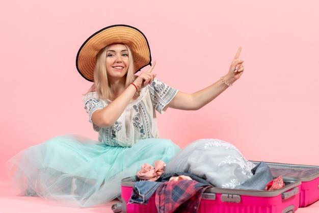 Vista frontale giovane donna che si prepara per il viaggio e smonta i suoi vestiti su sfondo rosa viaggio viaggio aereo marittimo resto vestiti di colore