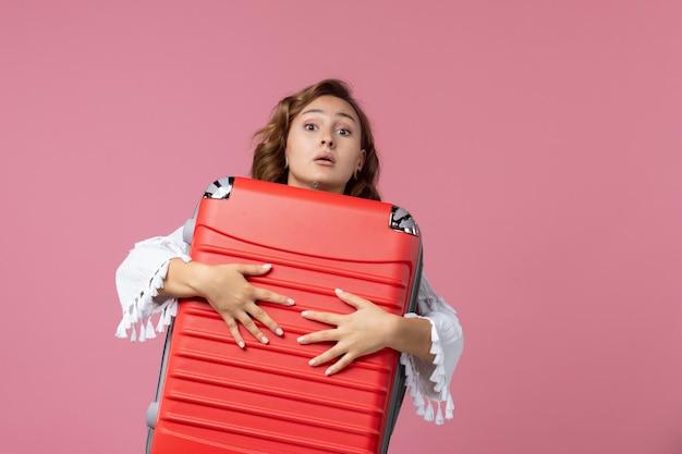 Vista frontale della giovane donna che si prepara per il viaggio e tiene in mano una borsa rossa sul muro rosa