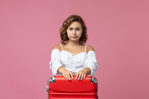 Vista frontale della giovane donna che si prepara per il viaggio con la sua borsa rossa sul muro rosa