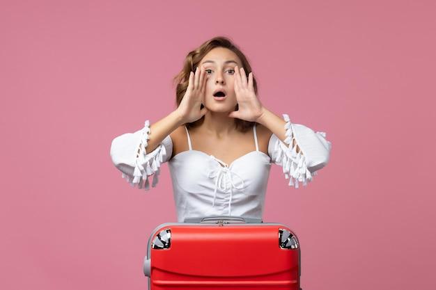 Vista frontale della giovane donna che si prepara per il viaggio con la borsa rossa che chiama il muro rosa