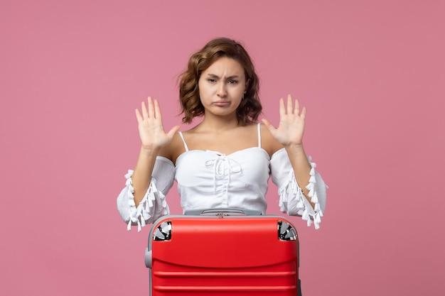 Vista frontale della giovane donna che si prepara per il viaggio con la borsa rossa sul muro rosa chiaro