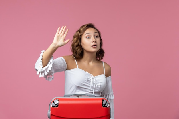 Vista frontale della giovane donna che si prepara per il viaggio con la borsa rossa sul muro rosa