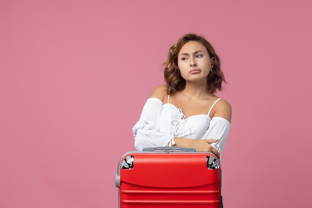 Front view of young woman preparing for trip with red bag on the pink wall