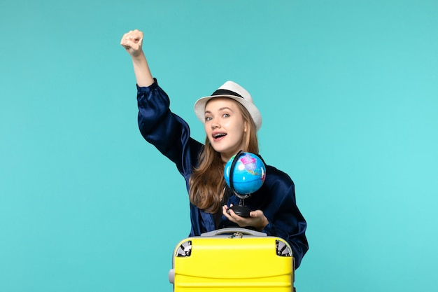 Front view young woman preparing for vacation and holding globe on blue desk plane voyage woman sea journey