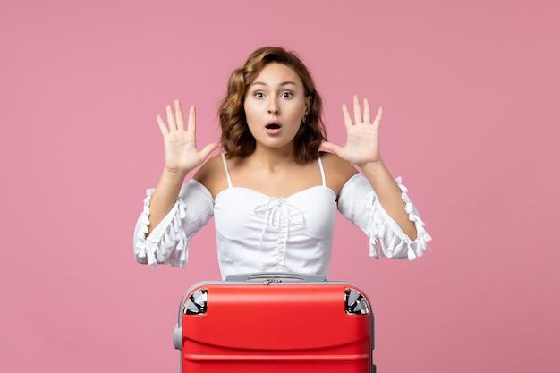 Vista frontale della giovane donna che si prepara per le vacanze con la borsa e posa sul pavimento rosa vacanza viaggio in mare modello viaggio colore