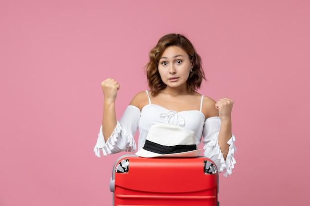 Vista frontale della giovane donna che si prepara per le vacanze con la borsa e posa sul muro rosa
