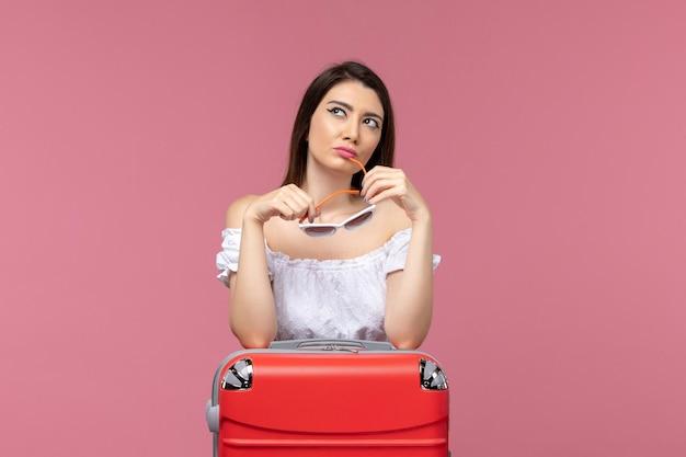 Vista frontale della giovane donna che prepara per le vacanze con la sua borsa pensando su sfondo rosa viaggio viaggio viaggio femminile mare all'estero