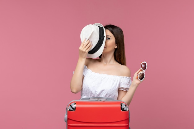 Front view young woman preparing for vacation with her hat on pink desk voyage trip journey abroad travel sea
