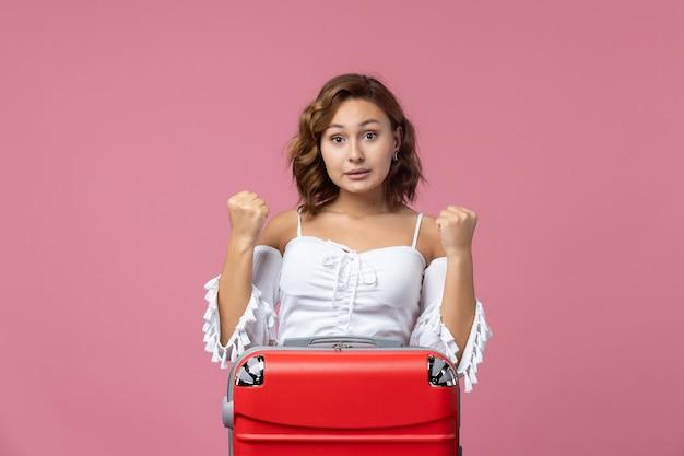 Vista frontale della giovane donna che si prepara per le vacanze con la sua borsa rossa sul muro rosa chiaro
