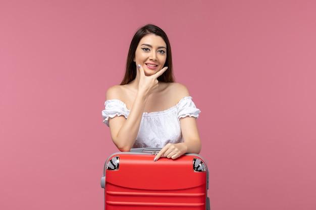 Giovane donna di vista frontale che prepara per la vacanza con la sua borsa rossa sulla donna di viaggio del mare di viaggio dello scrittorio rosa vacanza all'estero