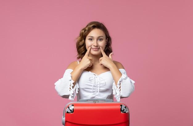 Vista frontale della giovane donna che si prepara per le vacanze con la sua borsa rossa sul muro rosa