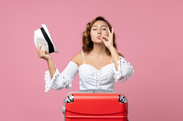 Front view of young woman preparing for vacation with red bag and posing on pink floor model color sea vacation voyage trip