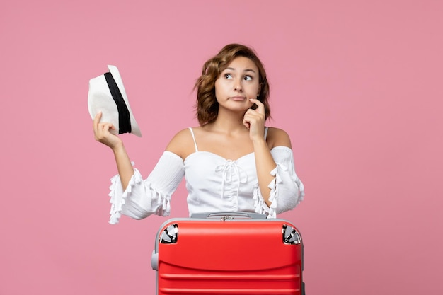 Front view of young woman preparing for vacation with red bag and posing on pink wall