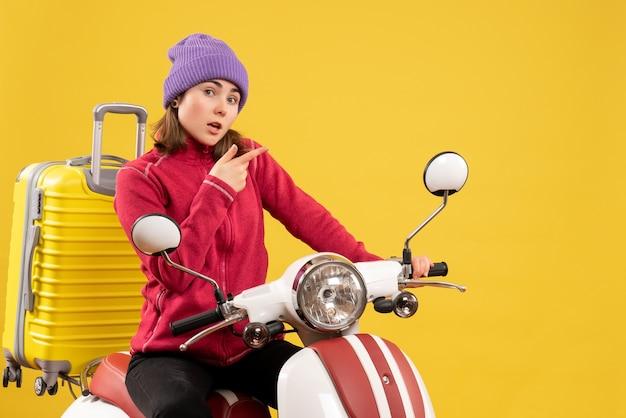 Giovane donna di vista frontale in cappello viola sul ciclomotore che indica qualcosa