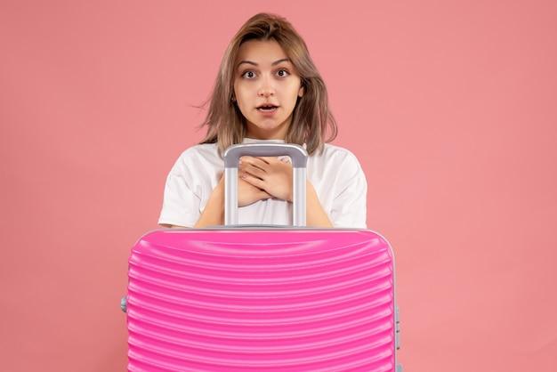 Giovane donna vista frontale che si mette le mani sul petto in piedi dietro una grande valigia