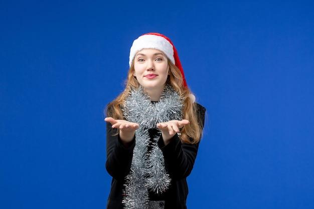 Vista frontale della giovane donna in berretto rosso con ghirlande sul muro blu