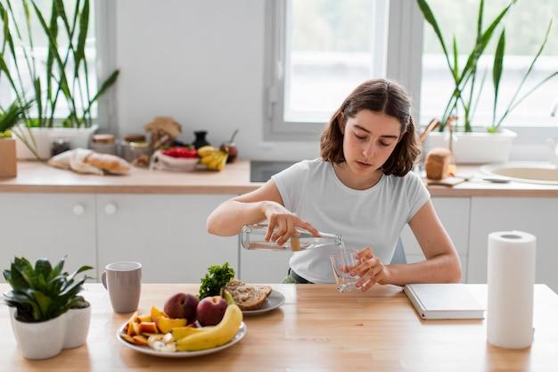 Молодая женщина, расслабляющаяся на кухне, вид спереди