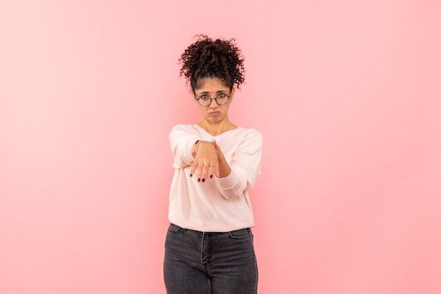 Front view of young woman sad on a pink wall