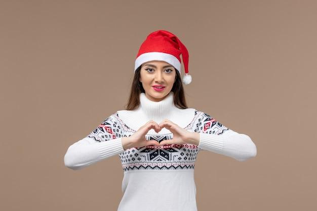 Вид спереди молодая женщина, отправляющая любовь на коричневом фоне, новогодние эмоции, рождество