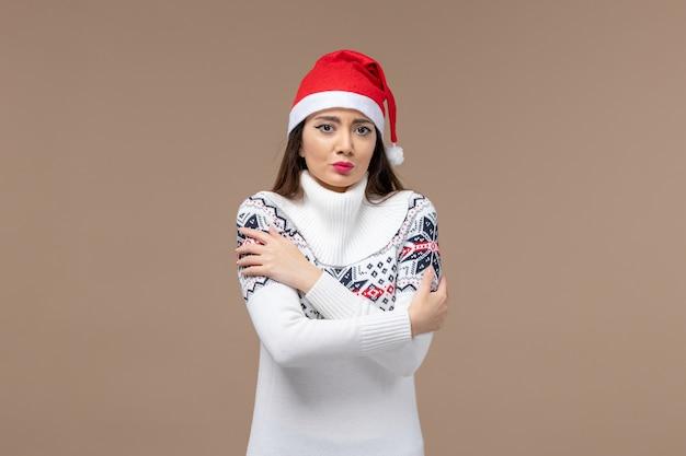 Вид спереди молодая женщина дрожит от холода на коричневом фоне новогодние эмоции рождество