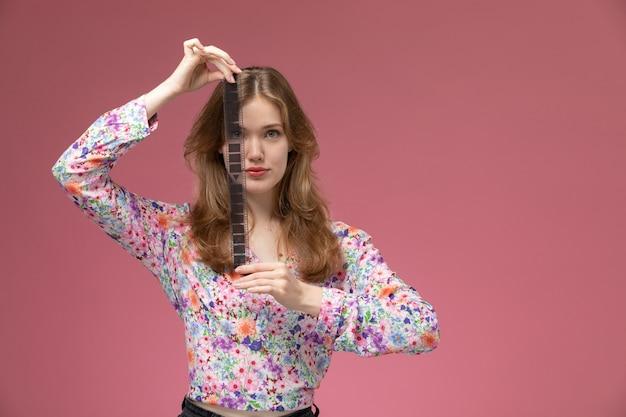 Вид спереди молодая женщина показывает кинопленку вертикально