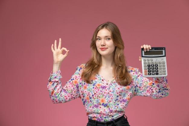 La giovane donna di vista frontale mostra che il calcolatore è abbastanza a posto