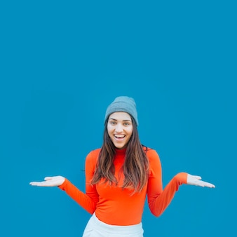 Front view of young woman shrugging her shoulder against blue backdrop