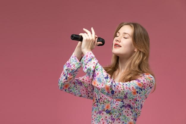 Giovane donna di vista frontale che canta con la sua voce di testa