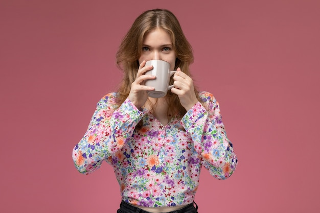 Front view young woman sipping her coffee