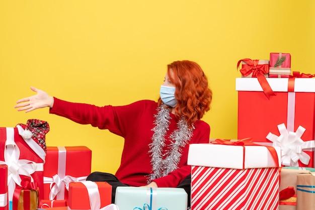 Vista frontale della giovane donna seduta intorno a regali di natale in maschera sulla parete gialla