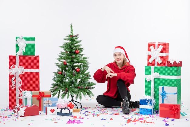 Vista frontale della giovane donna seduta intorno a diversi regali di festa sul muro bianco