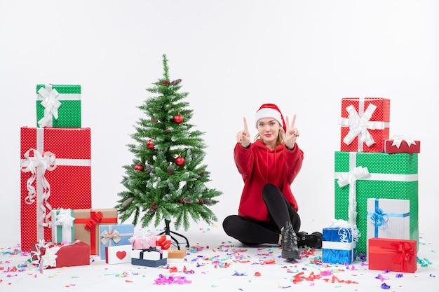 Vista frontale della giovane donna seduta intorno ai regali di festa contando sul muro bianco