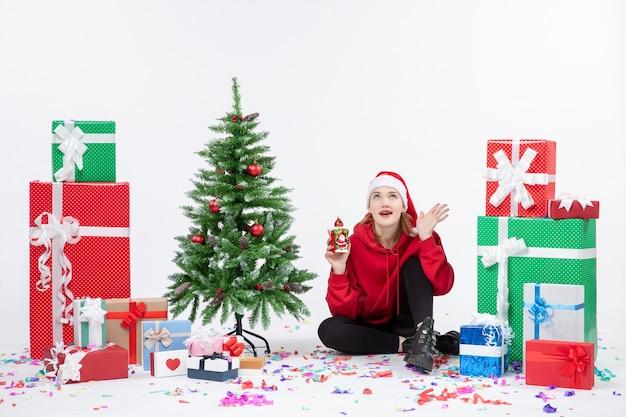 Vista frontale della giovane donna seduta intorno ai regali di festa in possesso di qualcosa sul muro bianco