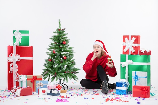 Front view of young woman sitting around holiday presents holding something on white wall