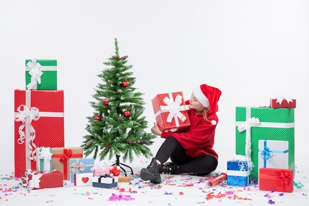 Vista frontale della giovane donna seduta intorno ai regali di festa sul muro bianco