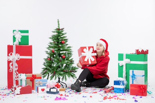 Front view of young woman sitting around holiday presents on white wall