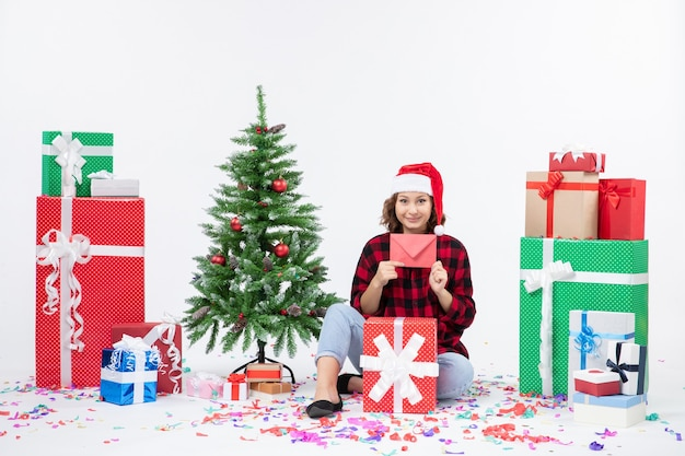 Front view of young woman sitting around presents holding envelop on white wall