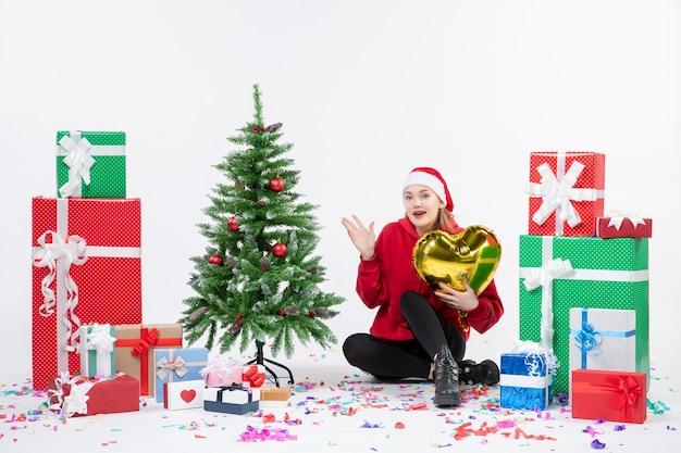 Vista frontale della giovane donna seduta intorno a regali che tengono la figura del cuore d'oro sul muro bianco