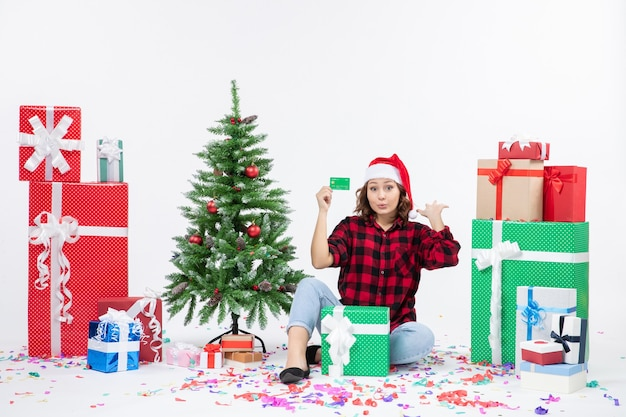 Front view of young woman sitting around presents holding green bank card on white wall