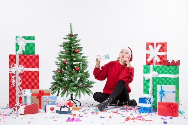Front view of young woman sitting around presents holding plane tickets on the white wall
