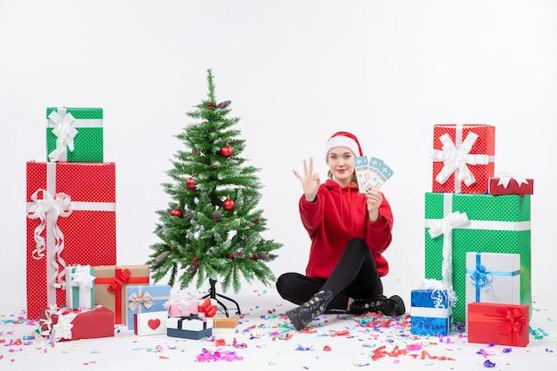Vista frontale della giovane donna seduta intorno a regali in possesso di biglietti aerei sul muro bianco