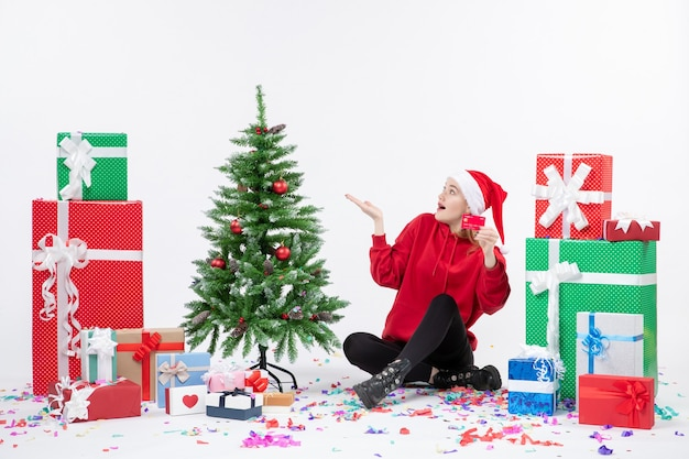 Front view of young woman sitting around presents holding red bank card on the white wall