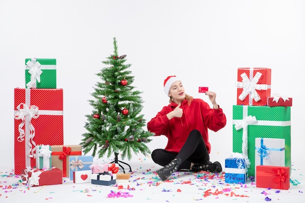 Front view of young woman sitting around presents holding red bank card on white wall