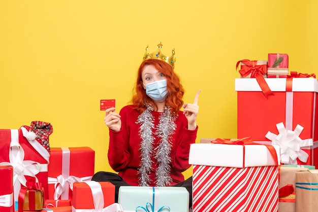 Front view of young woman sitting around presents in mask with bank card on a yellow wall
