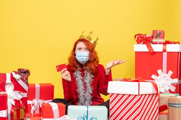 Front view of young woman sitting around presents in mask with bank card on the yellow wall