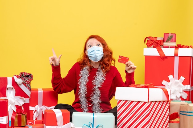 Front view of young woman sitting around presents in mask with bank card on yellow wall