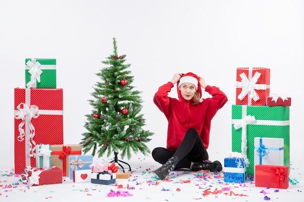 Vista frontale della giovane donna seduta intorno a regali sul muro bianco