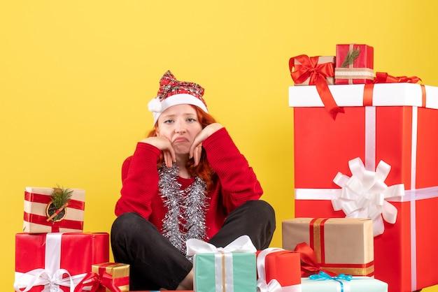 Vista frontale della giovane donna seduta intorno ai regali di natale annoiati su una parete gialla